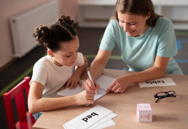 Młoda kobieta psycholog pomaga dziewczynie w terapii mowy
