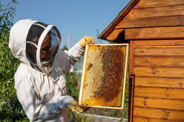 Młoda kobieta pszczelarz trzymać drewnianą ramę o strukturze plastra miodu