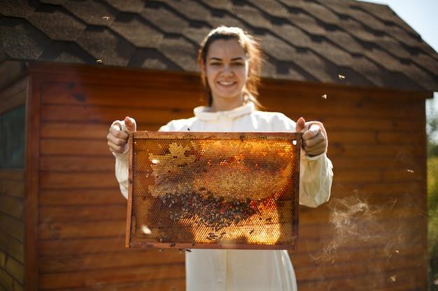 Młoda kobieta pszczelarz trzymać drewnianą ramę z plastra miodu
