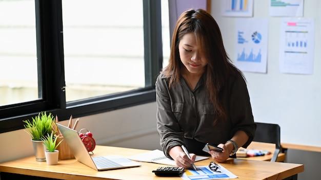 Młoda kobieta rachunkowości analizy dokumentów papierowych z posiadania telefonu komórkowego.