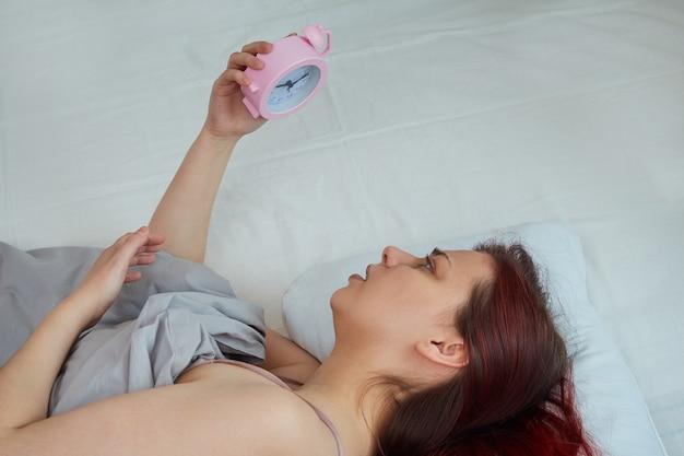 Młoda kobieta rano leży w łóżku i trzyma w dłoni budzik niezadowolona z wczesnego wstawania