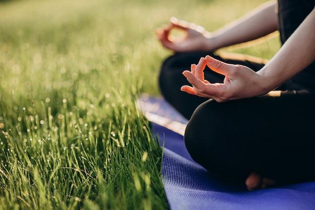 Młoda kobieta rasy kaukaskiej ćwiczy jogę w pozycji lotosu wczesnym słonecznym porankiem w lesie z trawą i rosą miękka selekcyjna ostrość.
