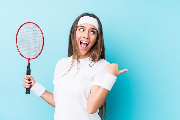 Młoda kobieta rasy kaukaskiej grając w badmintona pojedyncze punkty kciukiem palcem, śmiejąc się i beztrosko.