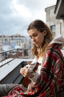 Młoda kobieta rasy kaukaskiej hipster / hipis w zwykłych ubraniach grających na hawajskiej gitarze śpiewa piosenkę na ukulele w domu na tarasie.