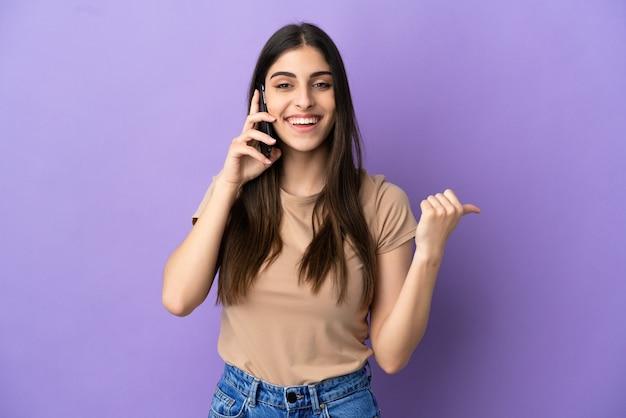 Młoda kobieta rasy kaukaskiej korzystająca z telefonu komórkowego odizolowanego na fioletowym tle wskazującego na bok, aby zaprezentować produkt