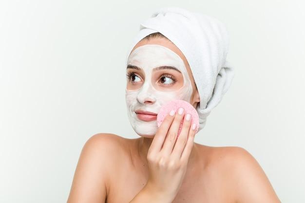 Młoda kobieta rasy kaukaskiej korzystających z zabiegów na twarz maski z dysku twarzy