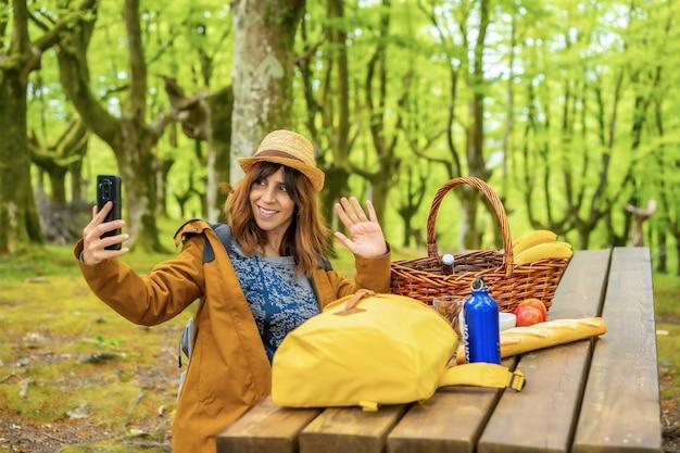 Młoda kobieta rasy kaukaskiej macha do telefonu siedząc przy stole piknikowym w lesie