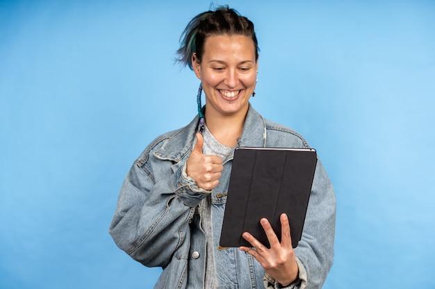 Młoda kobieta rasy kaukaskiej na rozmowie wideo i pokazująca gest zatwierdzenia na tablecie na niebieskiej ścianie