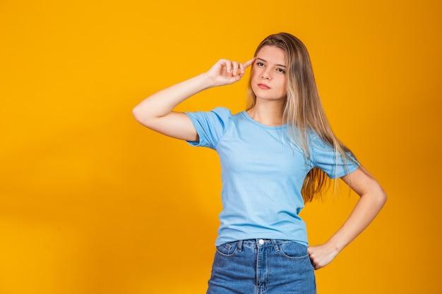 Młoda kobieta rasy kaukaskiej nad odosobnionym żółtym tłem, myśląca i patrząca w bok