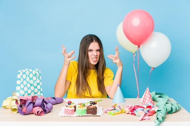 Młoda kobieta rasy kaukaskiej organizująca zdenerwowanie urodzinowe, krzycząca z napiętymi rękami.