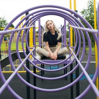 Młoda kobieta rasy kaukaskiej siedzi w kręgu wspinać się na placu zabaw