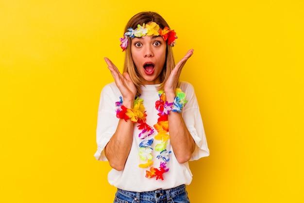 Młoda kobieta rasy kaukaskiej świętująca hawajską imprezę zaskoczona i zszokowana.