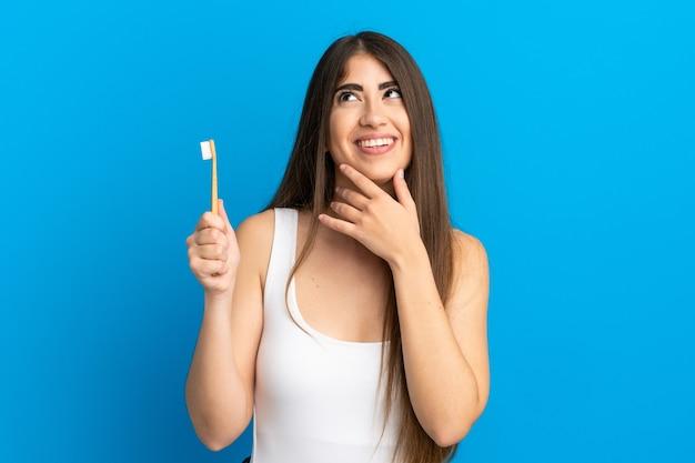 Młoda kobieta rasy kaukaskiej szczotkuje zęby na białym tle na niebieskim tle patrząc w górę podczas uśmiechania się