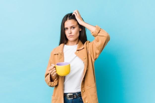 Młoda kobieta rasy kaukaskiej trzymająca kubek kawy, będąc w szoku, przypomniała sobie ważne spotkanie.