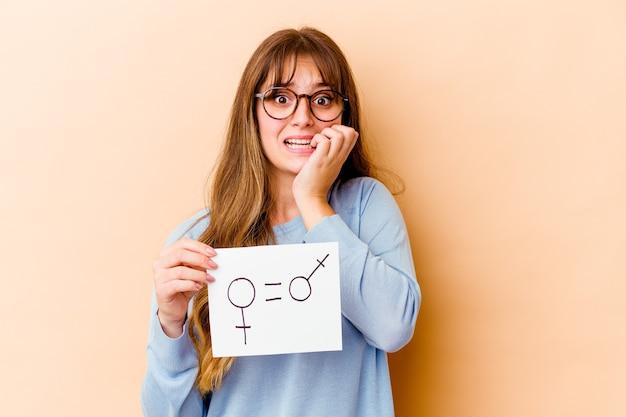 Młoda kobieta rasy kaukaskiej trzymająca plakietkę równości płci na białym tle gryząc paznokcie, nerwowa i bardzo niespokojna.