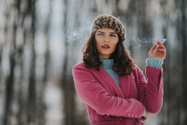 Młoda kobieta rasy kaukaskiej ubrana w różowy płaszcz i paląca papierosy w parku z drzewami w tle