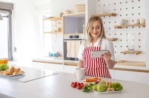 Młoda kobieta rasy kaukaskiej w czerwonym fartuchu w paski, trzymająca kubek patrząc na przepis na telefonie w kuchni