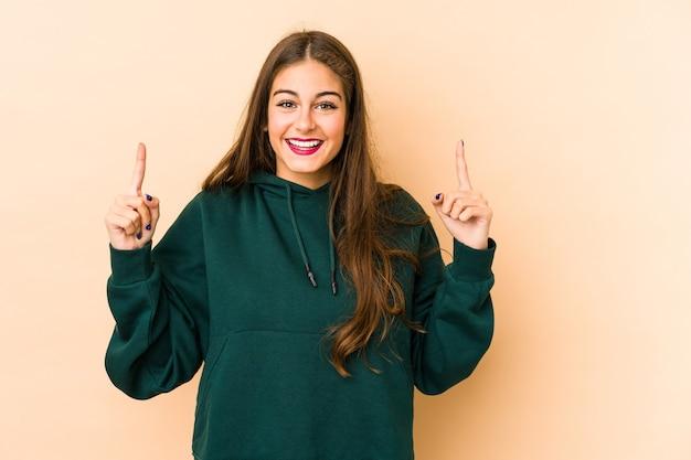 Młoda kobieta rasy kaukaskiej w kolorze beżowym wskazuje obiema przednimi palcami do góry, pokazując puste miejsce.