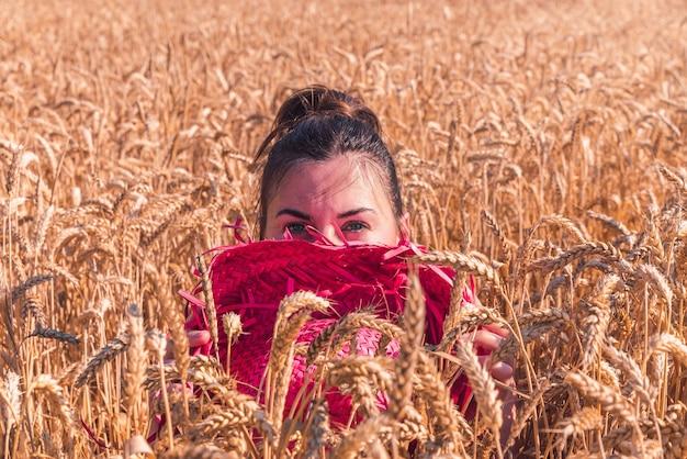 Młoda kobieta rasy kaukaskiej w pięknej czerwonej sukience, ciesząca się słoneczną pogodą na polu pszenicy