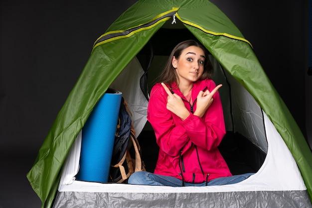 Młoda kobieta rasy kaukaskiej wewnątrz zielonego namiotu kempingowego, wskazując na części boczne, mając wątpliwości