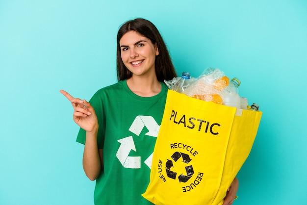 Młoda kobieta rasy kaukaskiej z recyklingu plastiku na białym tle na niebieskim tle, uśmiechając się i wskazując na bok, pokazując coś w pustej przestrzeni.