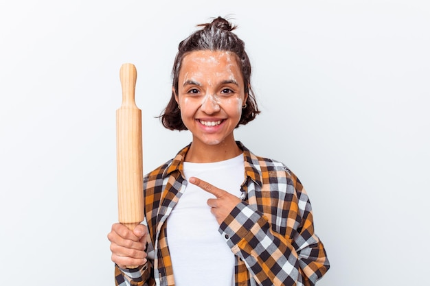 Młoda kobieta rasy mieszanej, co chleb na białym tle na białej ścianie, uśmiechając się i wskazując na bok, pokazując coś w pustym miejscu.