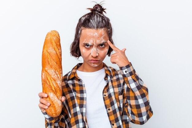 Młoda kobieta rasy mieszanej, co chleb na białym tle na białej ścianie, wskazując świątynię palcem, myśląc, koncentrując się na zadaniu.