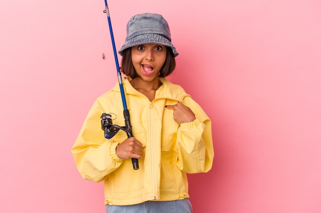 Młoda kobieta rasy mieszanej ćwicząca wędkarstwo na białym tle na różowym tle osoba wskazująca ręcznie na miejsce na koszulkę, dumna i pewna siebie