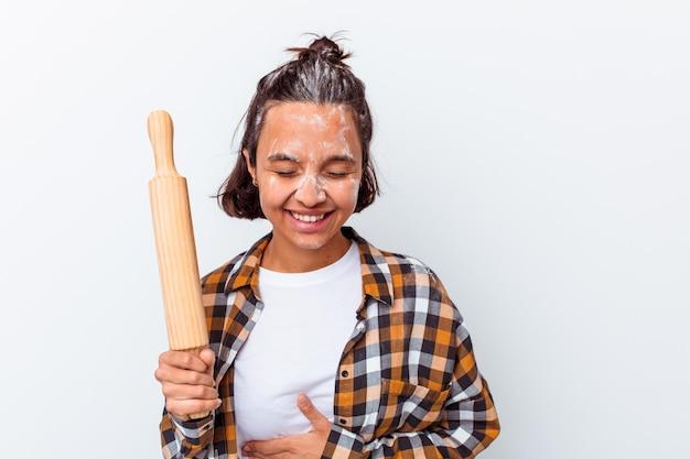 Młoda kobieta rasy mieszanej dokonywanie chleba na białym tle na białej ścianie śmiejąc się i zabawy.
