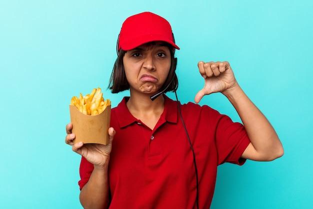 Młoda kobieta rasy mieszanej fast food restauracja pracownik gospodarstwa frytki na białym tle na niebieskim tle pokazując gest niechęci, kciuk w dół. koncepcja niezgody.