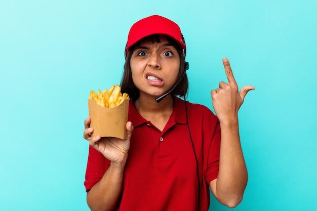 Młoda kobieta rasy mieszanej fast food restauracja pracownik gospodarstwa frytki na białym tle na niebieskim tle pokazując gest rozczarowania palcem wskazującym.