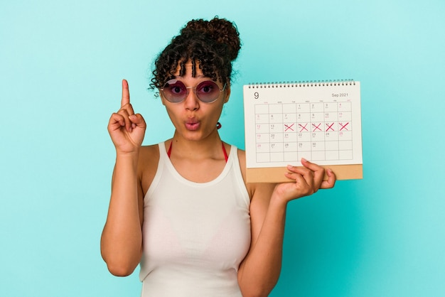 Młoda kobieta rasy mieszanej gospodarstwa kalendarz na białym tle na niebieskim tle o jakiś świetny pomysł, pojęcie kreatywności.