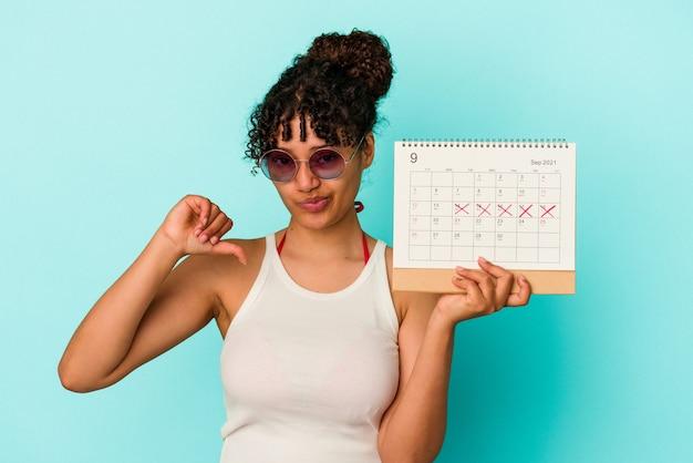 Młoda kobieta rasy mieszanej gospodarstwa kalendarz na białym tle na niebieskim tle pokazujący gest niechęci, kciuk w dół. koncepcja niezgody.