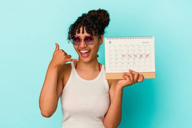 Młoda kobieta rasy mieszanej gospodarstwa kalendarz na białym tle na niebieskim tle pokazujący gest połączenia z telefonu komórkowego palcami.