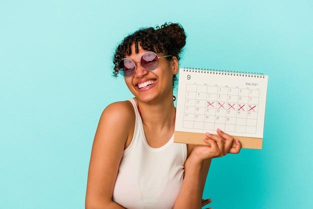 Młoda kobieta rasy mieszanej gospodarstwa kalendarz na białym tle na niebieskim tle śmiechu i zabawy.