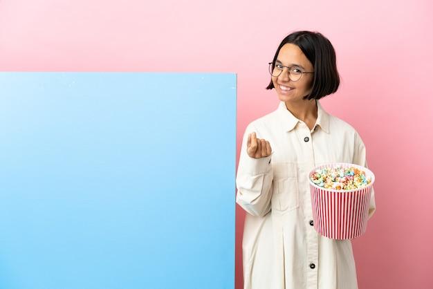 Młoda kobieta rasy mieszanej gospodarstwa popcorns z dużym sztandarem na białym tle, czyniąc gest pieniędzy