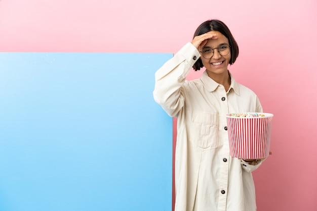 Młoda kobieta rasy mieszanej gospodarstwa popcorns z dużym sztandarem na białym tle salutowanie ręką z happy wypowiedzi