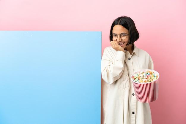 Młoda kobieta rasy mieszanej gospodarstwa popcorns z dużym sztandarem na białym tle szczęśliwa i uśmiechnięta obejmująca usta rękami