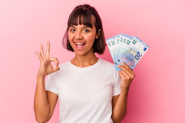 Młoda kobieta rasy mieszanej gospodarstwa rachunki na białym tle na różowym tle wesoły i pewny siebie, pokazując ok gest.