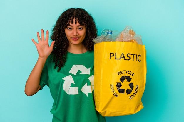 Młoda kobieta rasy mieszanej gospodarstwa recyklingu plastikową torbę na białym tle na niebieskim tle uśmiechnięty wesoły pokazując numer pięć palcami.