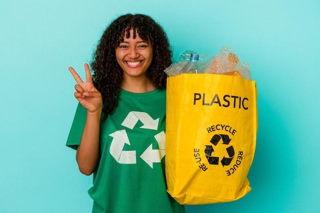 Młoda kobieta rasy mieszanej gospodarstwa recyklingu plastikowej torbie na białym tle na niebieskim tle pokazując numer dwa palcami.