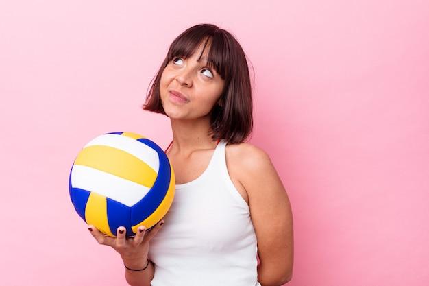 Młoda kobieta rasy mieszanej gra w siatkówkę na białym tle na różowym tle marząc o osiągnięciu celów i celów