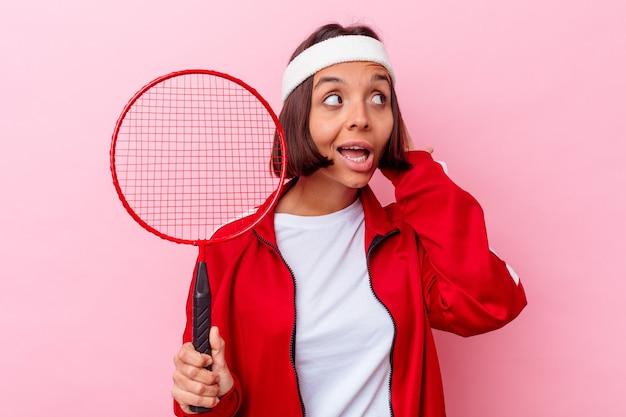 Młoda kobieta rasy mieszanej, grając w badmintona na białym tle na różowej ścianie, próbując słuchać plotek.