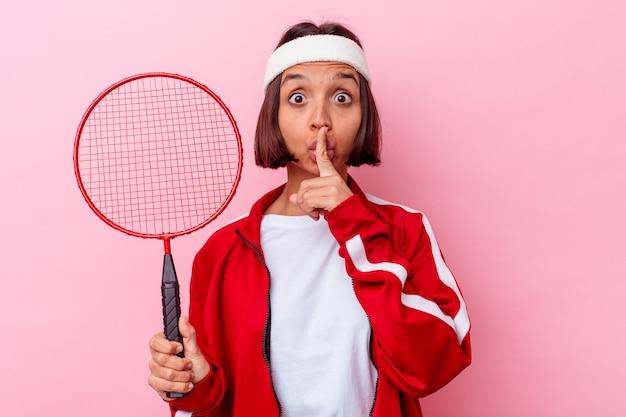 Młoda kobieta rasy mieszanej, grając w badmintona na białym tle na różowej ścianie, zachowując tajemnicę lub prosząc o ciszę.