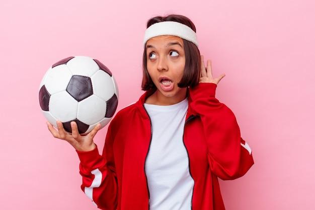 Młoda kobieta rasy mieszanej, grając w piłkę nożną na białym tle na różowej ścianie, próbując słuchać plotek.