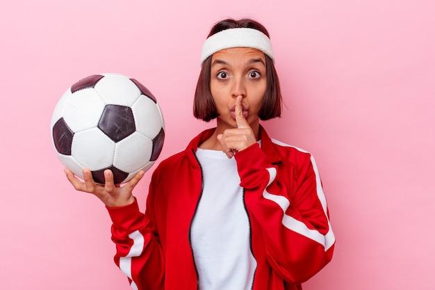 Młoda kobieta rasy mieszanej, grając w piłkę nożną na białym tle na różowej ścianie, zachowując tajemnicę lub prosząc o ciszę.
