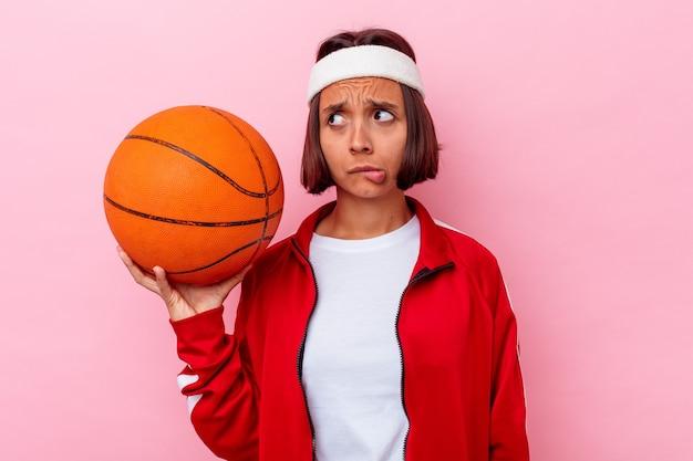 Młoda kobieta rasy mieszanej grająca w koszykówkę na różowej ścianie zdezorientowana, niepewna i niepewna.