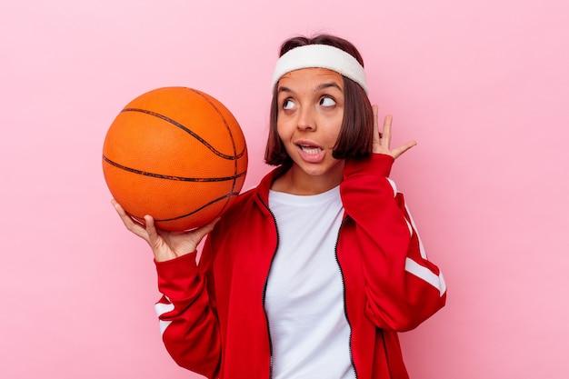 Młoda kobieta rasy mieszanej gry w koszykówkę na białym tle na różowej ścianie, próbując słuchać plotek.
