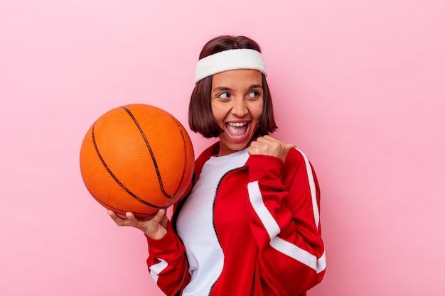 Młoda kobieta rasy mieszanej gry w koszykówkę na białym tle na różowej ścianie punkty z kciukiem z dala, śmiejąc się i beztrosko.