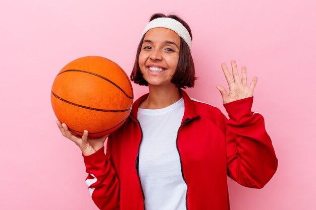 Młoda kobieta rasy mieszanej gry w koszykówkę na białym tle na różowej ścianie uśmiechnięty wesoły pokazując numer pięć palcami.